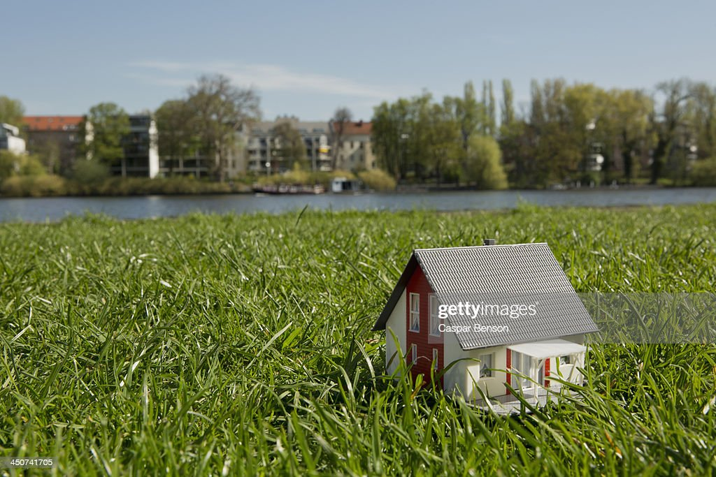 A miniature house on the lawn near the shore of a river : Photo