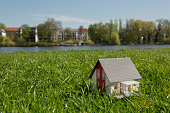 A miniature house on the lawn near the shore of a river