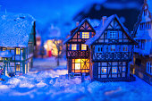miniature houses in the village covered by snow at night with light up decoration. Christmas winter model for holiday background with copy space for text.