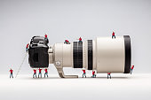 Miniature man woking with camera. Macro photo. the concept of work of a professional photographer