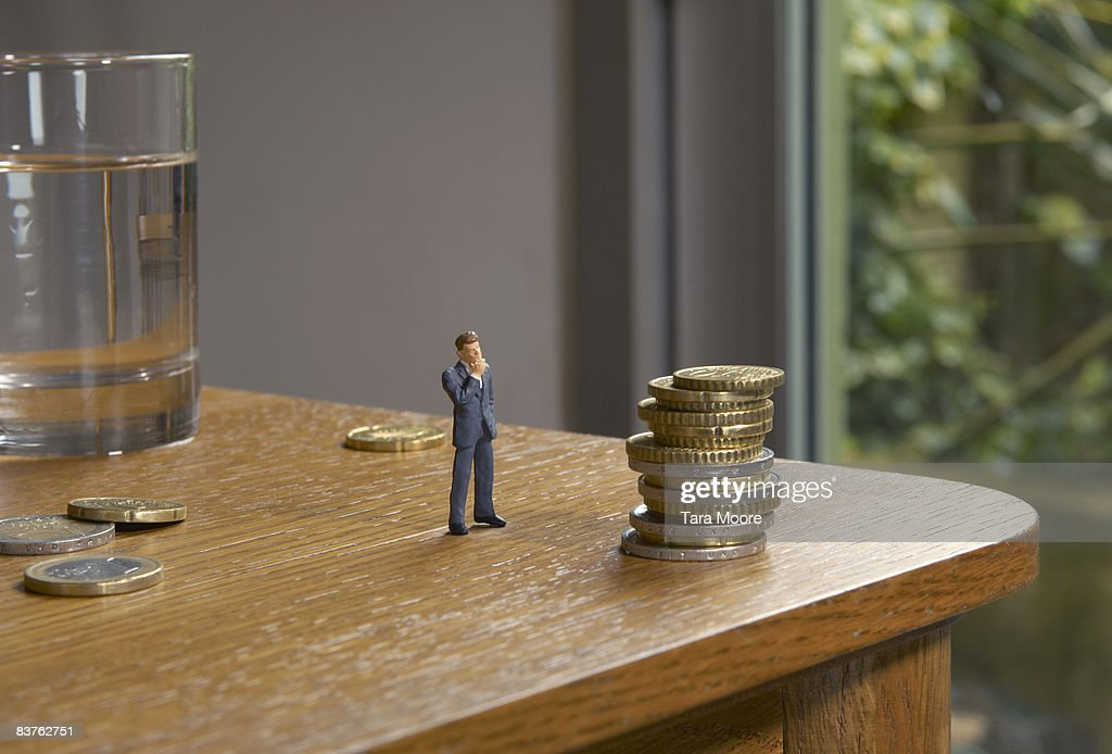 miniature man looking at pile of coins on table : Stock Photo