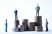 Miniature men on pile of coins