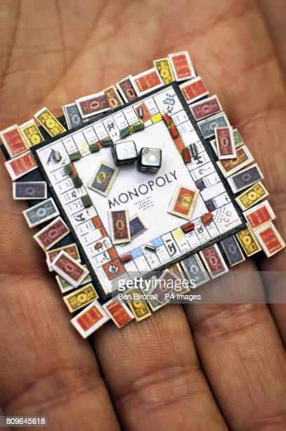 A miniature Monopoly board complete with houses cards and money made by Klaas Schultz of South Africa at the Karon Cunningham Miniatures shop in Bath