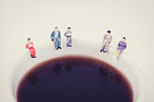 miniature people business team sitting on white coffee cup having a coffee break. business idea concept