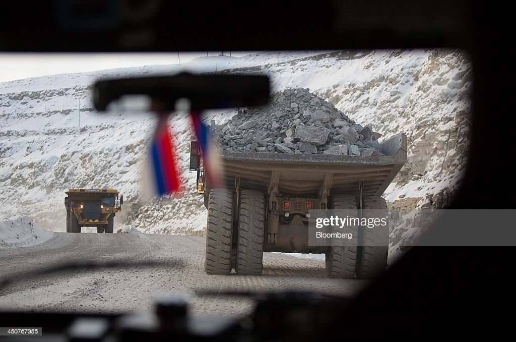 Miniature Russian flags hang from the rear view mirror of a vehicle following Caterpillar Inc. dump trucks as they transport excavated diamond ore from the open pit of the Nyurbinsky diamond mine operated by OAO Alrosa in Nakyn, Russia, on Friday, Nov. 15, 2013. OAO Alrosa, the world's largest diamond producer, raised about $1.3 billion in an oversubscribed share sale from investors including Oppenheimer Funds Inc. and Lazard Ltd.'s asset-management unit, First Deputy Prime Minister Igor Shuvalov said. Photographer: Andrey Rudakov/Bloomberg via Getty Images
