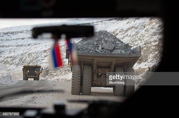 Miniature Russian flags hang from the rear view mirror of a vehicle following Caterpillar Inc dump trucks as they transport excavated diamond ore...