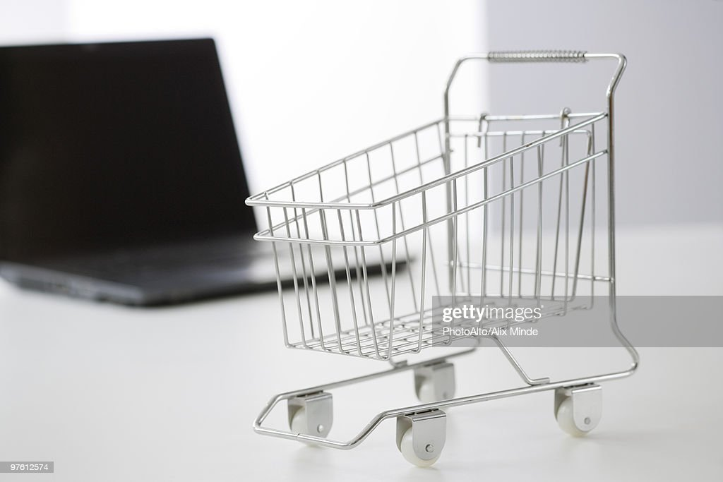 Miniature shopping cart and laptop computer : Stock Photo