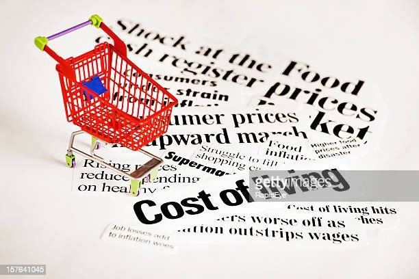Miniature shopping cart on headlines concerning cost of living