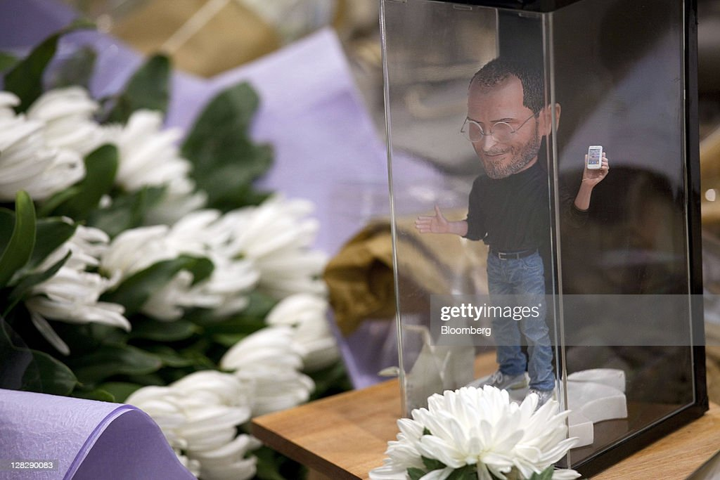 A miniature statue of Steve Jobs, co-founder and former chief executive officer of Apple Inc., and flowers are arranged outside Apple Inc. store in Hong Kong, China, on Thursday, Oct. 6, 2011. Jobs who built the world's most valuable technology company by creating devices that changed how people use electronics and revolutionized the computer, music and mobile-phone industries, died on Oct. 5. He was 56. Photographer: Jerome Favre/Bloomberg via Getty Images
