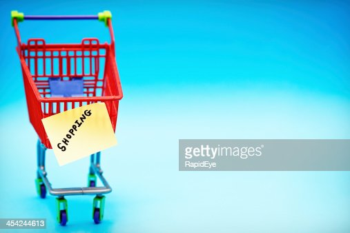 Miniature supermarket trolley with label saying Shopping : Stock Photo