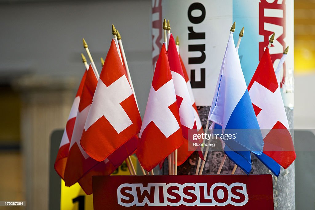 Miniature Swiss national flags sit displayed for sale outside a street vendor's stall in Lucerne, Switzerland, on Saturday, Aug. 10, 2013. The Swiss National Bank will abolish its franc ceiling once it starts raising interest rates, Vice President Jean-Pierre Danthine said. Photographer: Gianluca Colla/Bloomberg via Getty Images