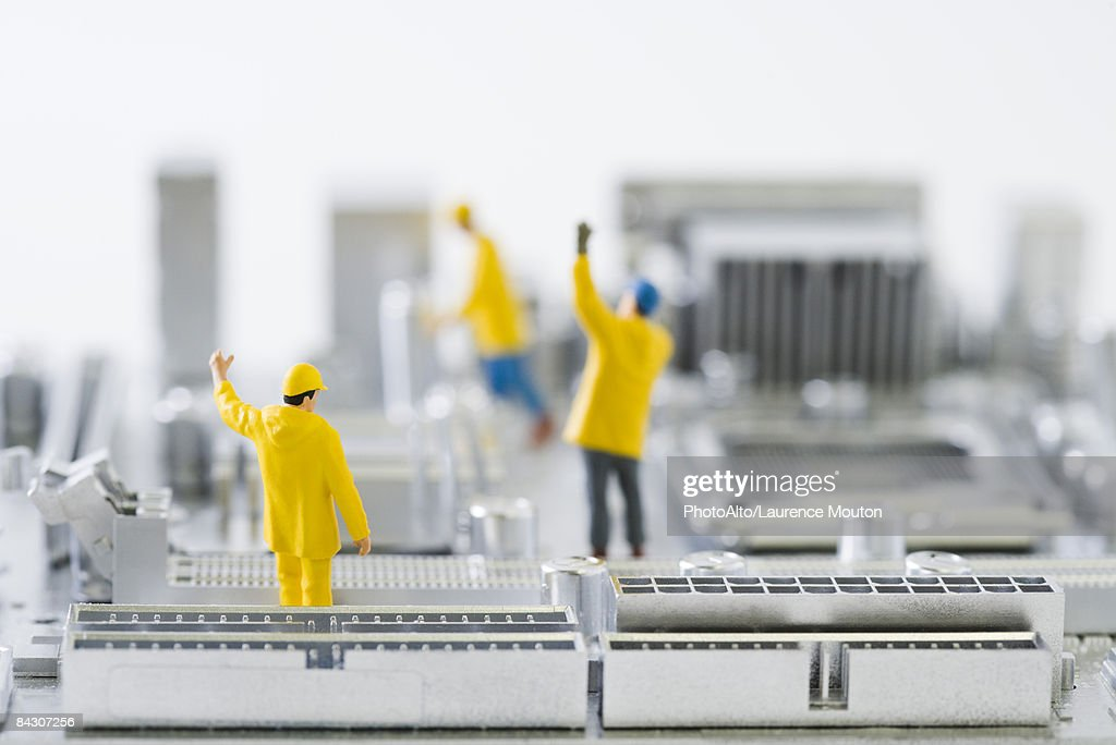 Miniature technicians standing on computer motherboard with arms raised