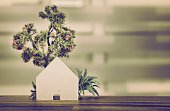 Miniature tree and house on wood surface