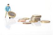 Miniature worker drives euro coins in wheelbarrow