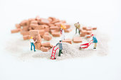 Miniature workmen doing construction brickwork