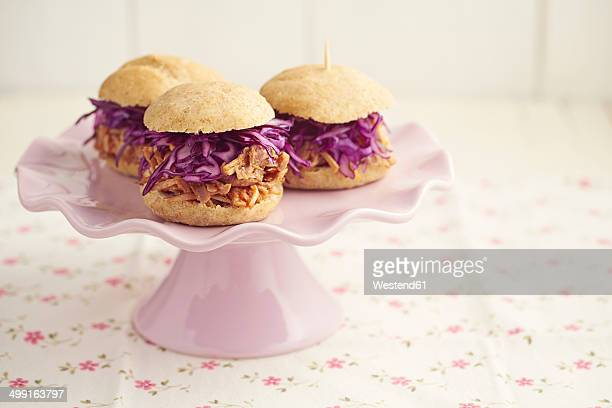 Mini-Burger with pulled pork, red cabbage and fried onions on cake stand