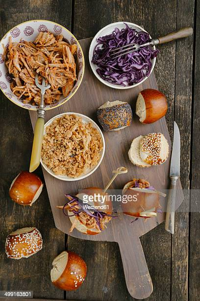 Mini-Burger with pulled pork, red cabbage and fried onions on chopping board