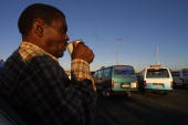 A minibus tax owner drinks an early morning cup of coffee at a taxi rank in Khayelitsha Cape Town 29 January 2004 Safety has become a major problem...
