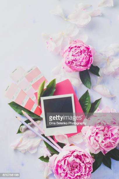 Minimal styled flat lay with peony flowers, blank photo frame and pink notebook.