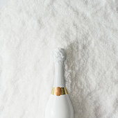 Minimal white champagne bottle in snow. New Year holiday party concept. Flat lay.