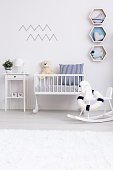 White minimalist room for baby with rocking horse and cradle