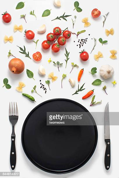 Minimalist flat lay cutlery set with plate, fresh vegetables, herbs and spices on white background.