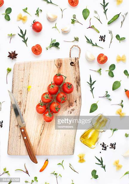 Minimalist flat lay wooden chopping board, fresh vegetables, herbs and spices on white background.