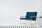 A minimalist living room interior with a white empty wall, elegant royal blue armchair with a metal golden frame and a striped rug