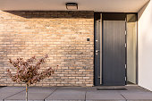 Minimalist clean red brick home exterior with black front door
