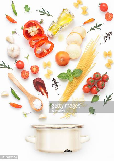 Minimalist style flat lay pasta recipe ingredients and cooking pot on white background.