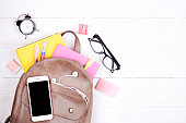 Hipster grey leather backpack, full of school supplies, blank screen cell phone, earphones, pink & yellow notebook, glasses, mini alarm clock. Back to school concept. Close up, copy space, flat lay.