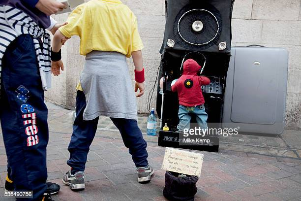 Minimix a street perfomance / where a man / busker hiding in a speaker operates a miniature DJ working hihs decks and playing big beat and hip hop...