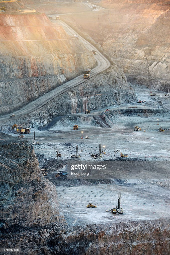 Mining trucks and machinery operate in the Fimiston Open Pit, known as the Super Pit, in Kalgoorlie, Australia, on Monday, Aug. 5, 2013. The Super Pit is managed by Kalgoorlie Consolidated Gold Mines Ltd., jointly owned by Barrick Gold Corp., the world's largest producer of the metal, and Newmont Mining Corp., the second-largest gold producer. Photographer: Carla Gottgens/Bloomberg via Getty Images