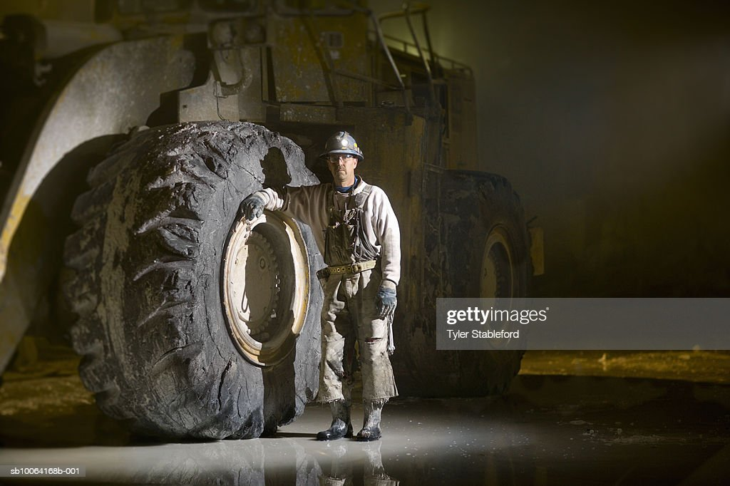 Mining worker standing beside tyre in marble quarry : Stock Photo