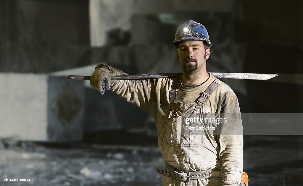 Mining worker standing with iron lever, portrait