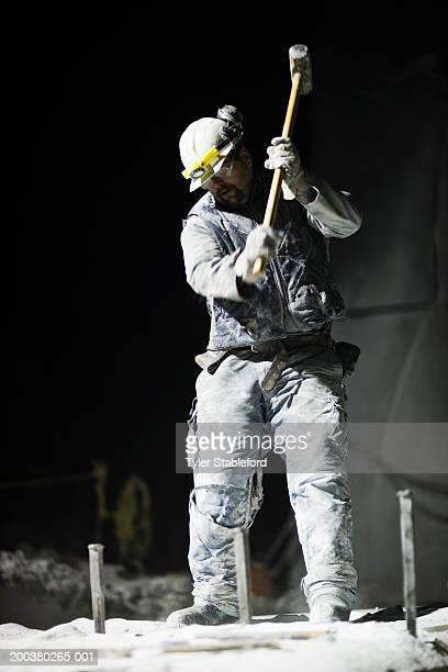 Mining worker swinging sledgehammer in stone quarry