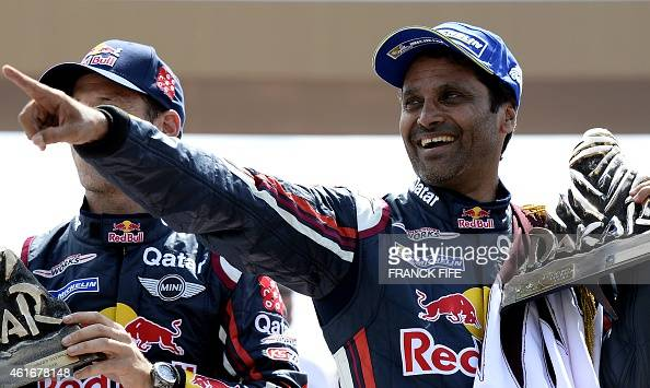 Mini's driver Nasser AlAttiyah from Qatar and codriver Mathieu Baumel from France raise the trophy on the podium of the 2015 Rally Dakar in Buenos...