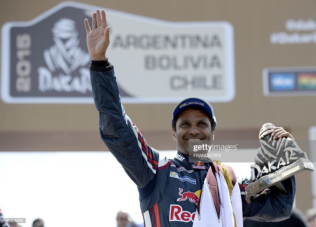 Mini's driver Nasser AlAttiyah of Qatar holds the trophy on the podium of the 2015 Rally Dakar in Buenos Aires Argentina on January 17 2015 AlAttiyah...