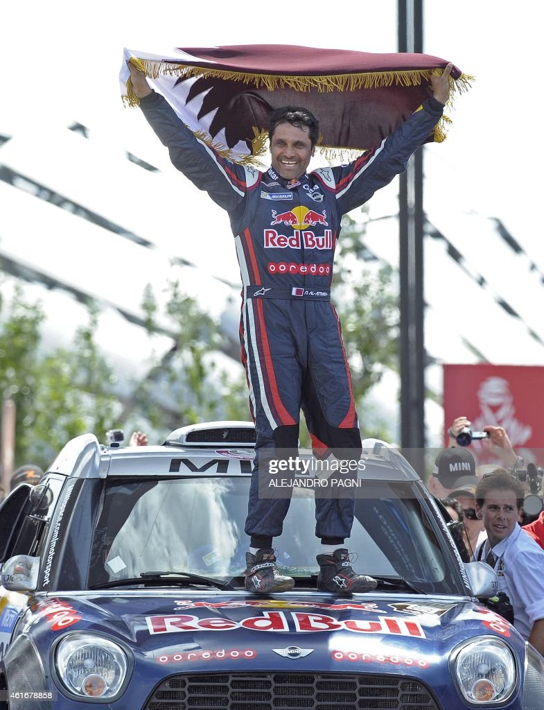 Mini's driver Nasser AlAttiyah of Qatar winner of the 2015 Dakar Rally auto category holds a Qatar flag as celebration on the podium in Buenos Aires...