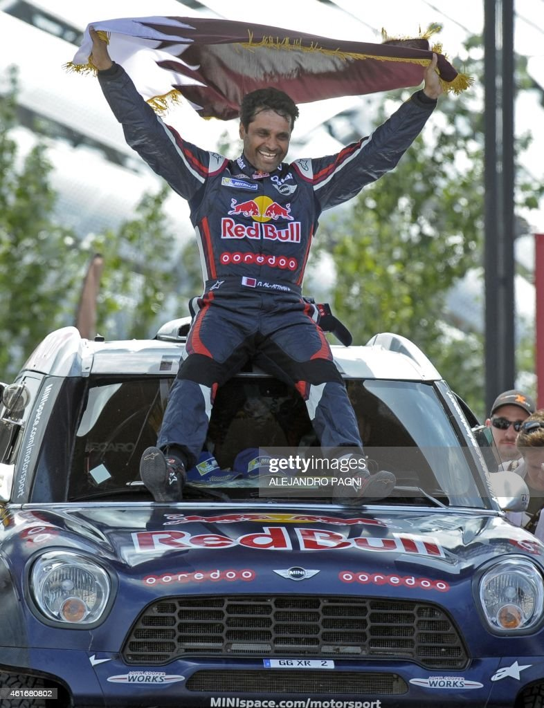 Mini's driver Nasser AlAttiyah of Qatar winner of the 2015 Dakar Rally car category holds a Qatar flag as he celebrates on the podium in Buenos Aires...