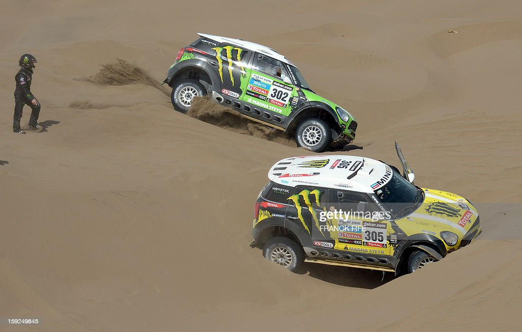 Mini's driver Stephane Perterhansel (C) of France passes next to Mini's driver Nani Joan Roma of Spain (R) during the Stage 6 of the Dakar 2013 between Arica and Calama, Chile, on January 10, 2013. The rally takes place in Peru, Argentina and Chile from January 5 to 20.
