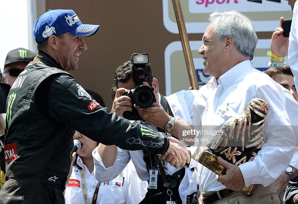 Mini's driver Stephane Peterhansel (L) of France receives his trophy from Chile's President Sebastian Pinera (R), on the podium of the 2013 Dakar Rally in Santiago, Chile on January 20, 2013. Mini's driver Stephane Perterhansel won the Dakar 2013 ahead of Toyota's driver Giniel De Villiers of South Africa and Mini's driver Leonid Novitskiy of Russia. AFP PHOTO / FRANCK FIFE