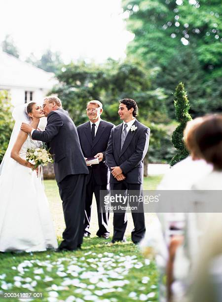 Minister and groom watching as father kisses bride on cheek, smiling
