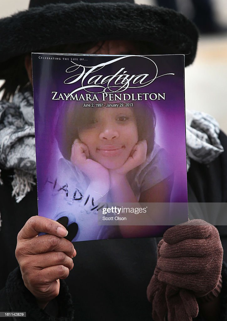 Minister Elnor Brown hold up a funeral program outside the Greater Harvest M.B. Church during the funeral of 15-year-old Hadiya Pendleton on February 9, 2013, in Chicago, Illinois. Hadiya was killed on January 29, when a gunman opened fire on her and some friends while they were standing under a shelter on a warm rainy afternoon in a park about a mile from President Obama's Chicago home. First lady Michelle Obama attended the funeral with Senior White House Adviser Valerie Jarrett and Secretary of Education Arne Duncan.