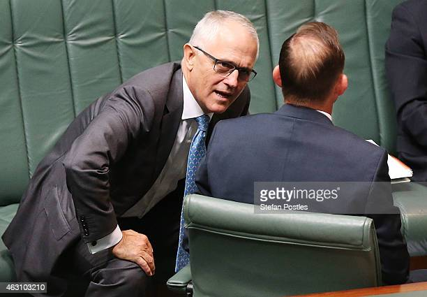 Minister for Communications Malcolm Turnbull speaks with Prime Minister Tony Abbott during House of Representatives question time at Parliament House...