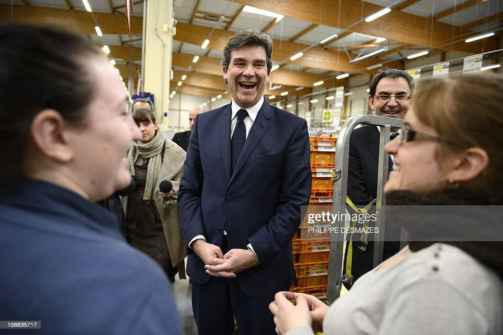 Minister for Industrial Renewal Arnaud Montebourg (C) jokes with workers as he visits a mail sorting office of 'La Poste' in Saint-Priest near Lyon, on December 31, 2012.