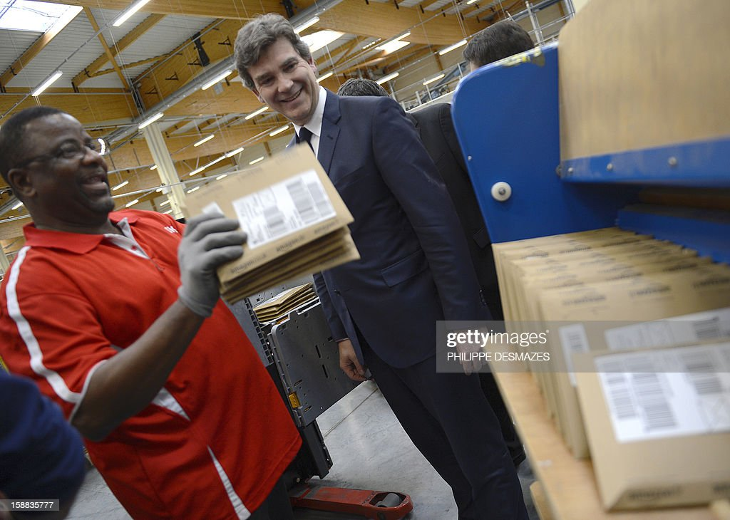 Minister for Industrial Renewal Arnaud Montebourg (C) smiles as he stands next to a worker during his visit to the mail sorting office of 'La Poste' in Saint-Priest near Lyon, on December 31, 2012.