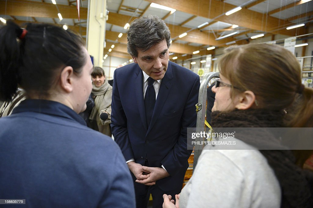 Minister for Industrial Renewal Arnaud Montebourg (C) talks with workers as he visits a mail sorting office of 'La Poste' in Saint-Priest near Lyon, on December 31, 2012.