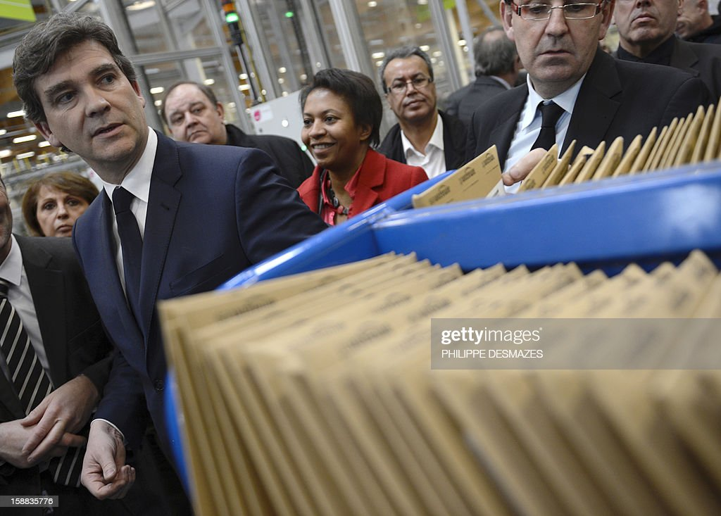 Minister for Industrial Renewal Arnaud Montebourg (L) walks past a pile of mail cards as he visits a mail sorting office of 'La Poste' in Saint-Priest near Lyon, on December 31, 2012.