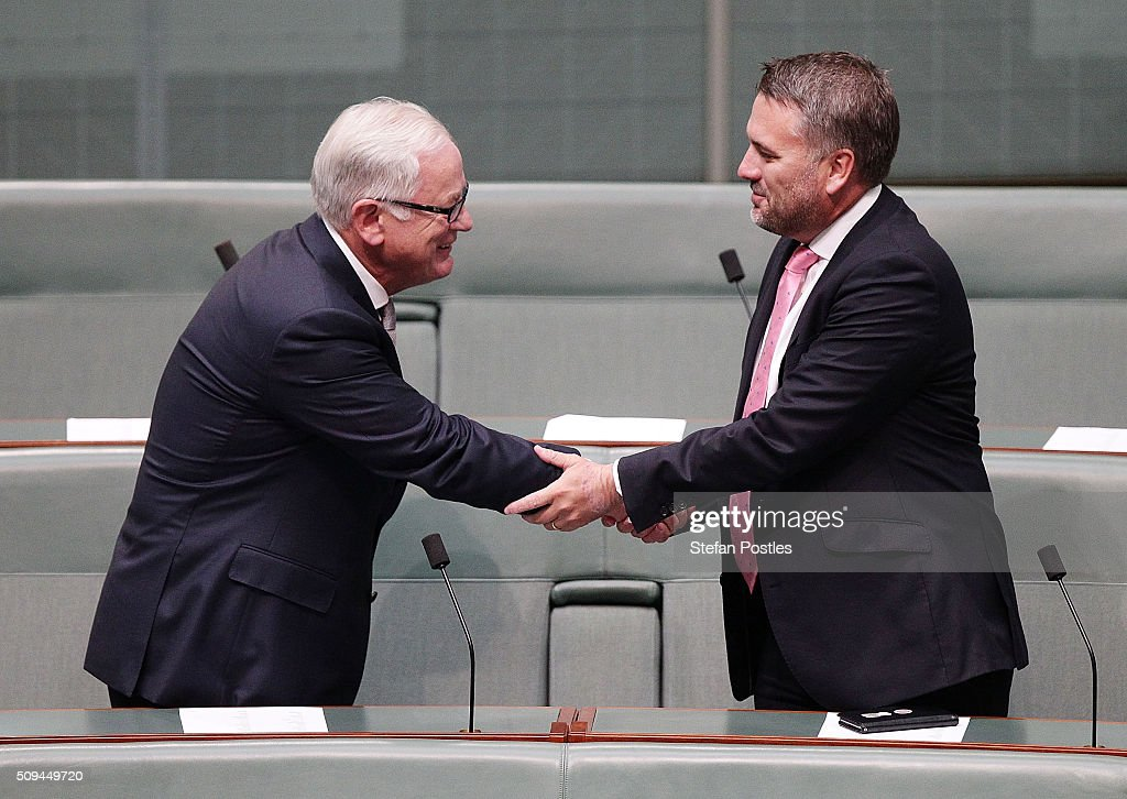 Minister for Trade and Investment Andrew Robb shakes hands with Jamie Briggs in the House of Representatives on February 11, 2016 in Canberra, Australia. Nationals Leader and Deputy Prime Minister Warren Truss and Trade Minister Andrew Robb will retire at the next election.